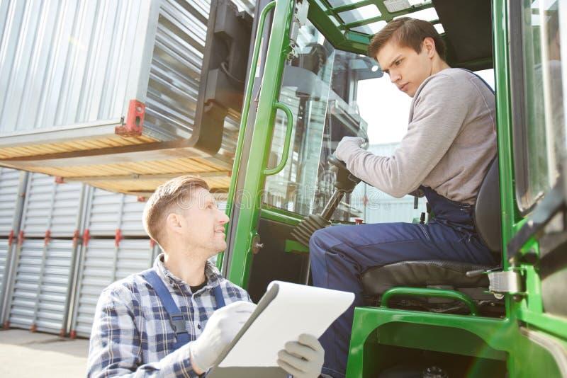 货物工头谈话与年轻铲车司机 库存照片
