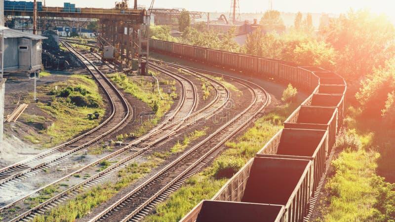 货物货车无盖货车在阳光下在铁路去在有植物和重工业的制造业工厂的工业区 免版税库存图片