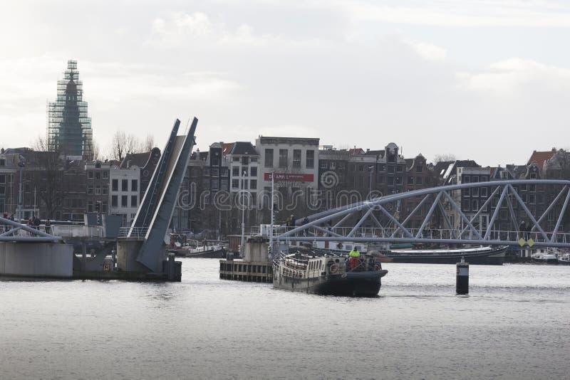 货船去低谷开放J J van der维尔德桥梁在背景Prins Hendrikkade阿姆斯特丹中荷兰 免版税库存图片