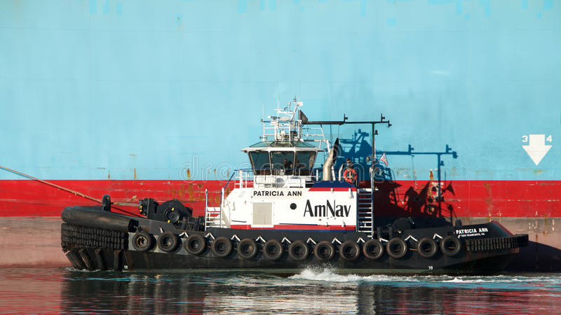 货船马士基ANTARES的左舷的拖轮帕特里夏ANN 免版税库存照片