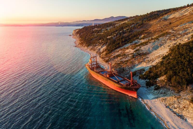货船鸟瞰图在狂放的海岸,在风暴以后的海难搁浅 免版税库存图片
