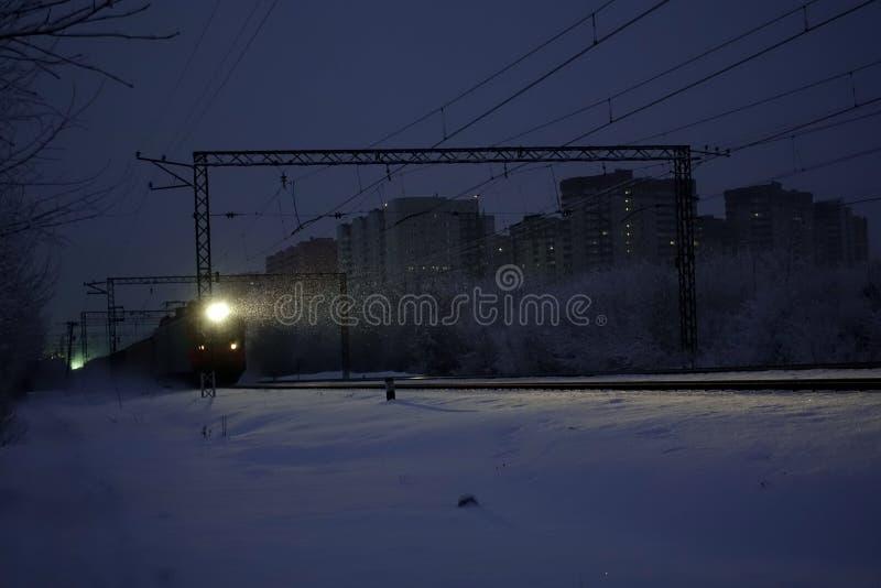 货车在晚上 车灯和机车车灯照亮落的雪 俄国 免版税库存照片