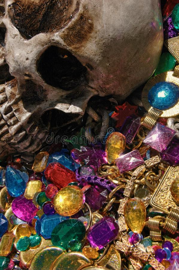 贪婪、头骨在堆珠宝中和金子梦想  免版税库存图片