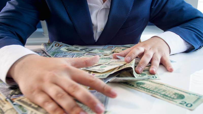 贪婪的说谎在办公桌上的商人劫掠的金钱特写镜头照片  图库摄影