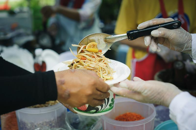 贫寒分享从更加亲切的社会的食物解除饥饿:恶劣人分享的社会概念:概念 免版税库存图片
