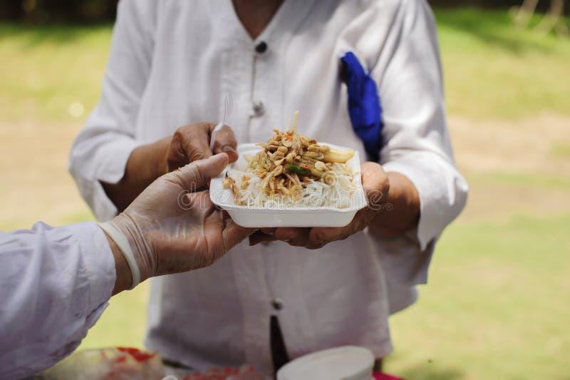 贫寒分享从更加亲切的社会的食物解除饥饿:恶劣人分享的社会概念:概念 库存图片