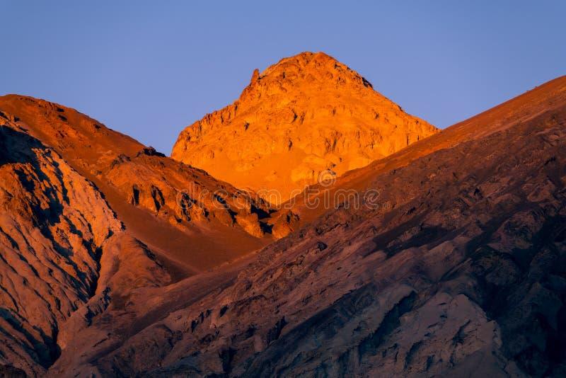 贫瘠,坚固性沙漠发光在日落金黄光的风景和高山  库存照片