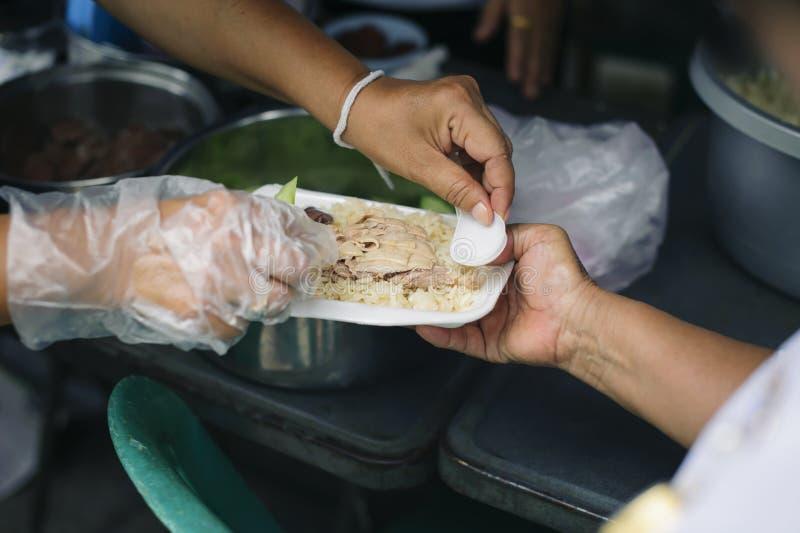 贫穷的概念在亚裔社会的:志愿者对解除饥饿的贫寒的份额食物 免版税图库摄影