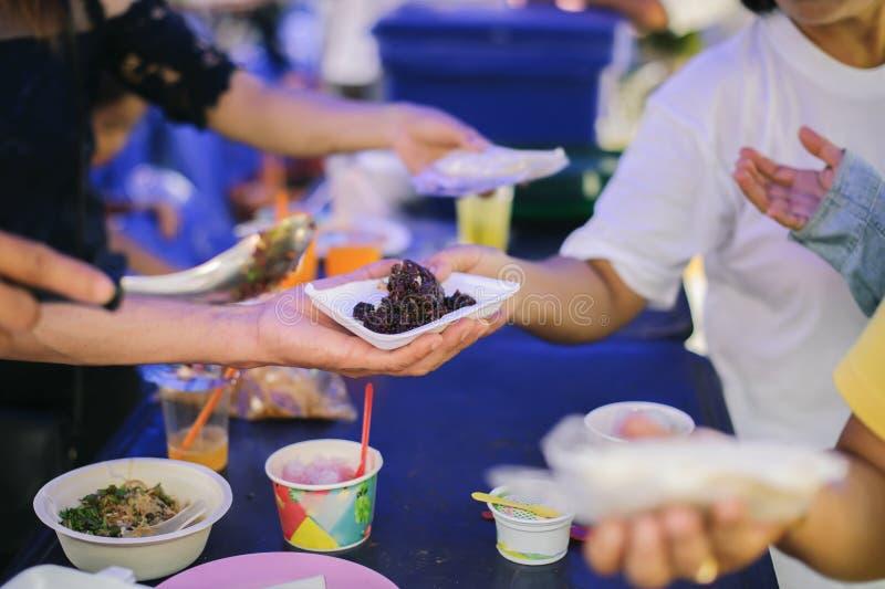 贫穷的概念在亚裔社会的:志愿者对解除饥饿的贫寒的份额食物 库存照片