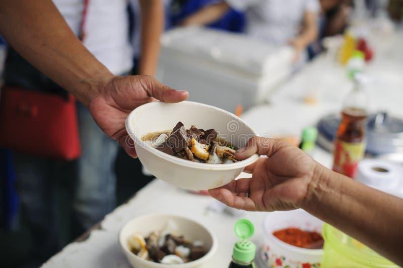贫穷的概念在亚裔社会的:志愿者对解除饥饿的贫寒的份额食物 免版税库存照片