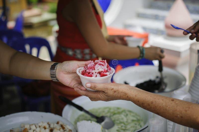 贫穷的概念在亚裔社会的:志愿者对解除饥饿的贫寒的份额食物 库存图片