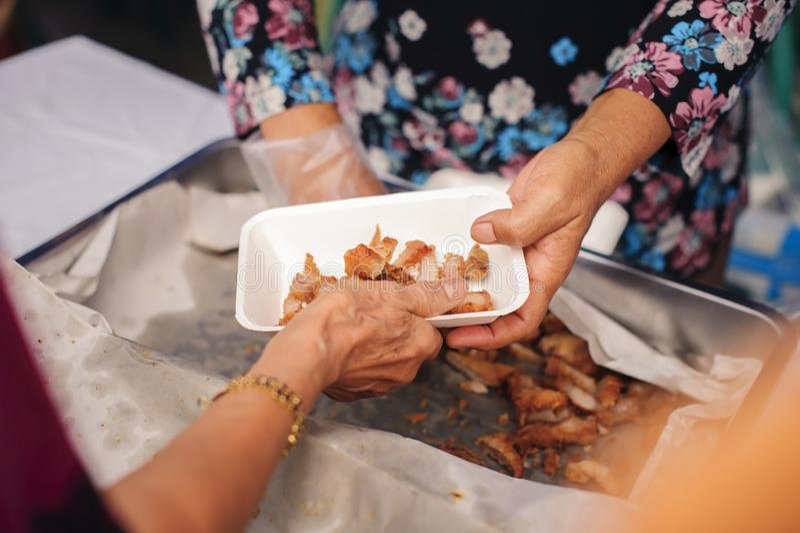 贫穷的概念在亚裔社会的:慈善食物为人是免费在贫民窟 库存图片