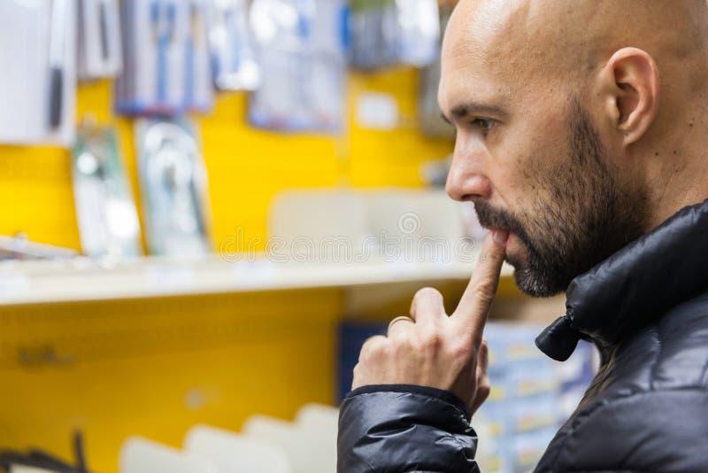 购买一套手工工具的年轻人在硬件商店 免版税库存图片