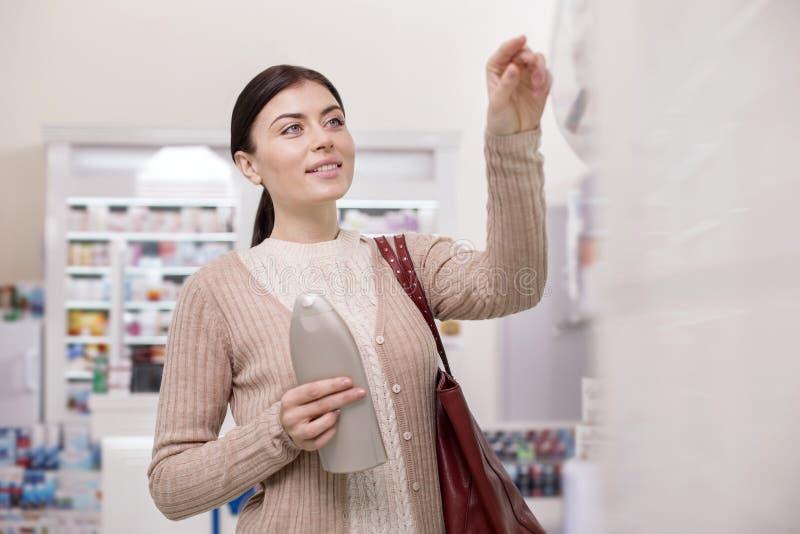 购买产品的半信半疑的女性客户 免版税库存照片