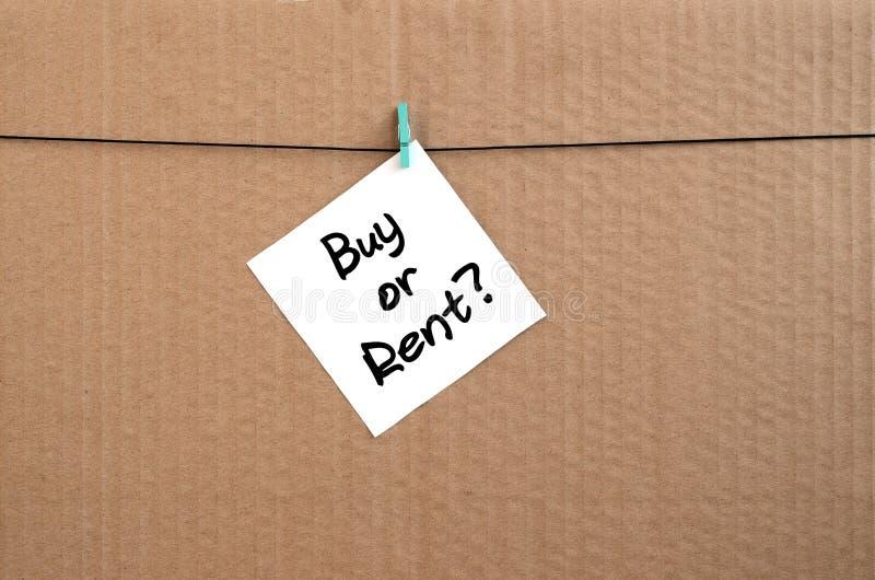 购买或租?笔记在垂悬的一个白色贴纸被写 库存图片