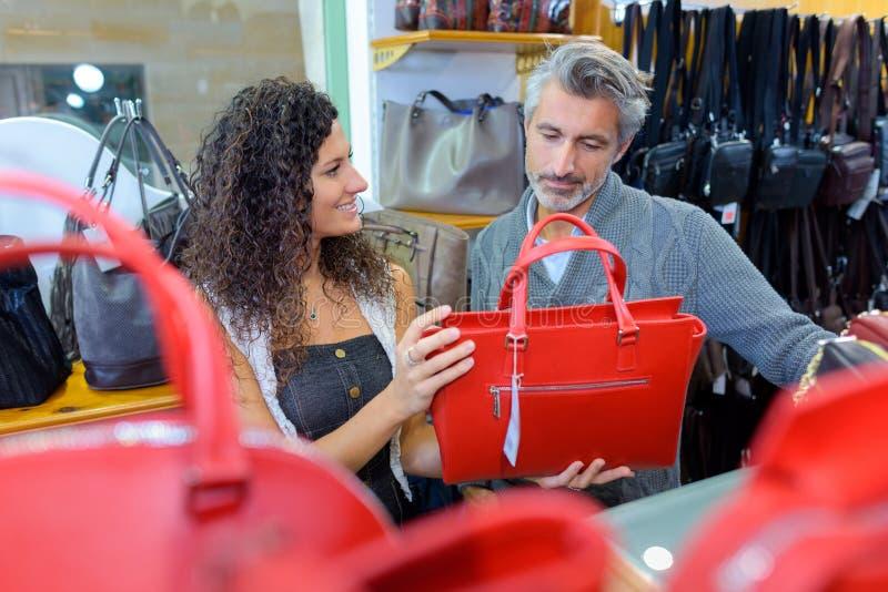 购买新的手袋的女性顾客在商店 免版税库存照片