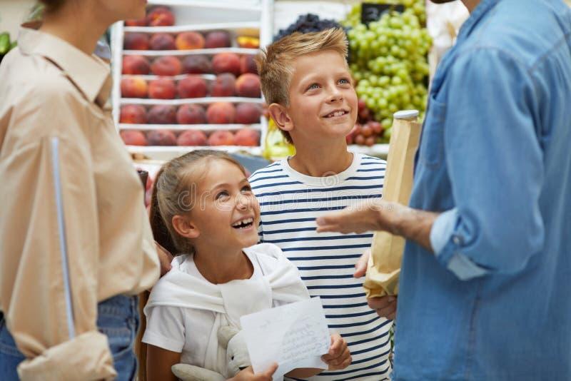 购物与父母的愉快的孩子在超级市场 免版税库存照片