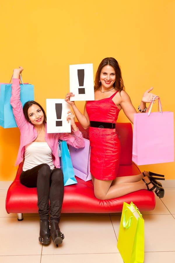 购物中心与颜色袋子和惊叹号的女孩与标志 库存照片