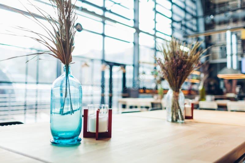 购物中心咖啡馆室内设计 用花瓶装饰的表有很多与蜡烛的干燥玻璃 免版税图库摄影