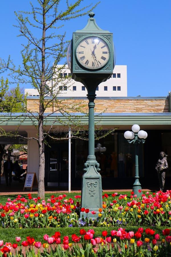 购物中心在有华丽街道时钟和明亮的郁金香的早期的春天 库存图片