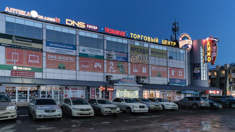 购物中心门面大厦夜视图和汽车在商店前面的停车场停放了 库存照片