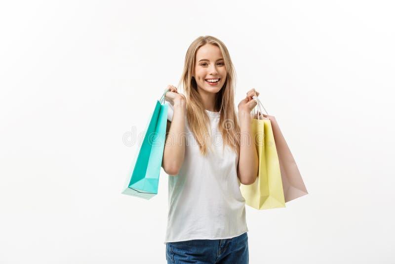 购物和生活方式概念:微笑和拿着购物袋的年轻愉快的夏天购物妇女被隔绝在白色 免版税库存图片