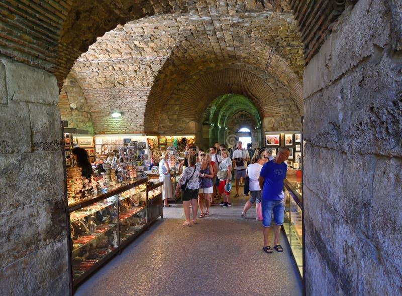 购物在商店在Diocletian罗马宫殿下,分裂克罗地亚的游人 免版税库存图片