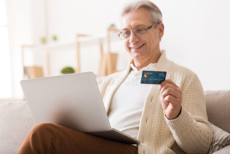 购物在网上在有信用卡的膝上型计算机的成熟人 免版税库存图片
