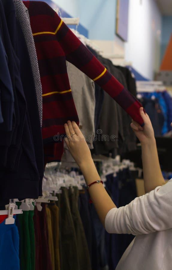 购物妇女,手观察立场毛线衣,孩子在商店 免版税库存照片