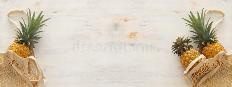 购物带来用在白色木背景的菠萝 r r 库存图片