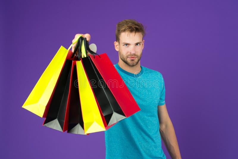 购物或销售和网络星期一 有购物袋的人在紫罗兰色背景 有五颜六色的纸袋的强壮男子 时尚顾客 免版税库存照片