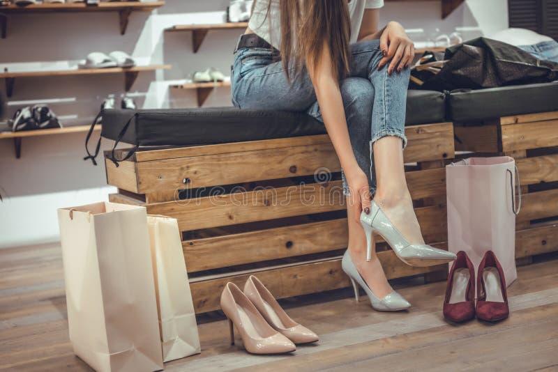 购物时间!尝试在年轻女人的鞋子坐长凳在商店背景 图库摄影