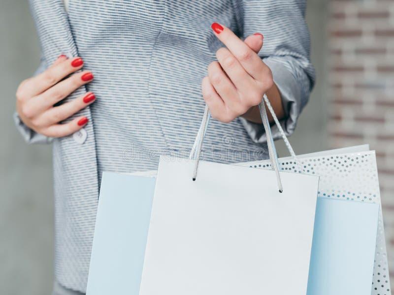 购物的季节中间销售妇女运载多个袋子 库存照片