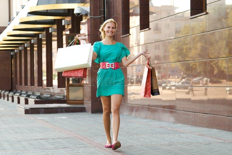 购物的微笑的走的妇女 图库摄影