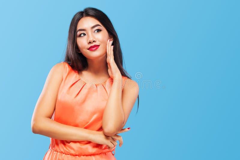 购物的愉快的亚裔妇女考虑销售的隔绝在蓝色背景黑星期五假日 复制空间为 免版税库存照片