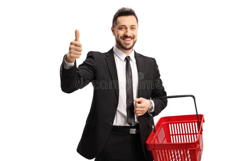 购物篮的商人笑着和拇指竖起 免版税图库摄影
