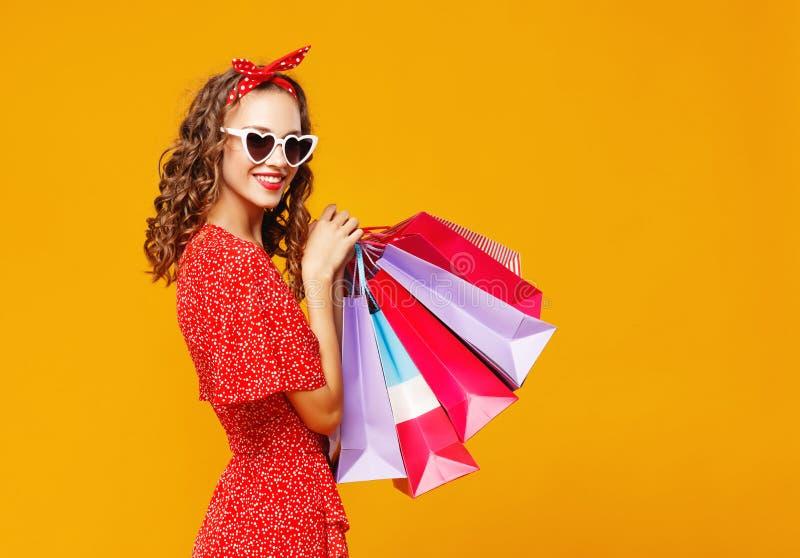 购物购买的愉快的女孩概念和销售有包裹的在黄色背景 库存图片