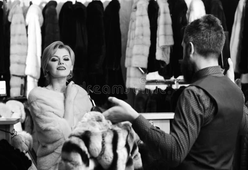 购物顾问概念 桃红色皮大衣的女孩在男性手上看镶边毛皮 有胡子的售货员和 图库摄影