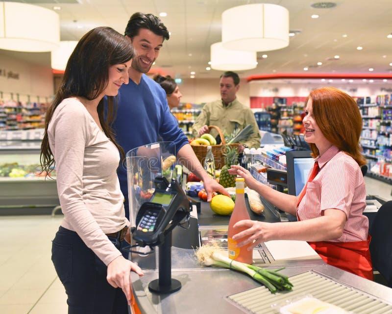 购物食物的人们在超级市场 免版税库存照片