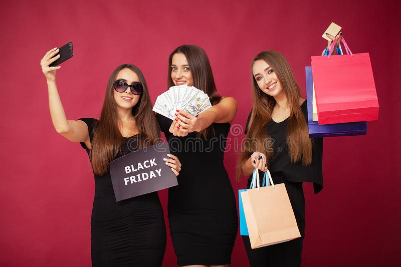 购物 拿着在红色背景的三名妇女折扣空白在黑星期五假日 免版税库存照片