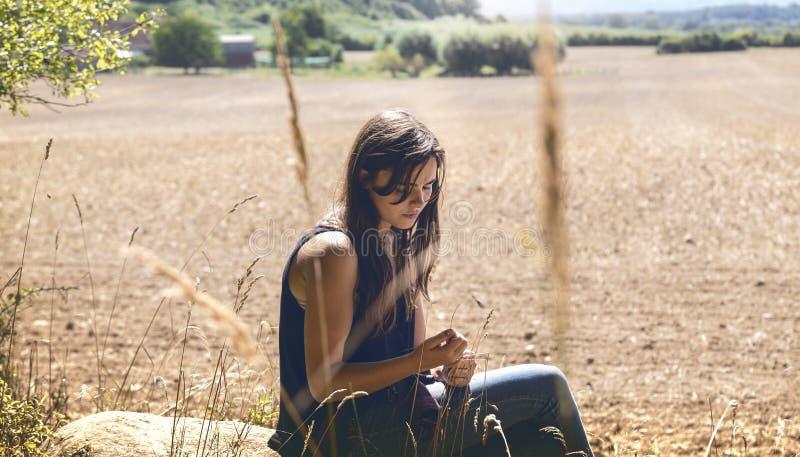 贴心的可怜女孩坐在岩石上 免版税库存照片