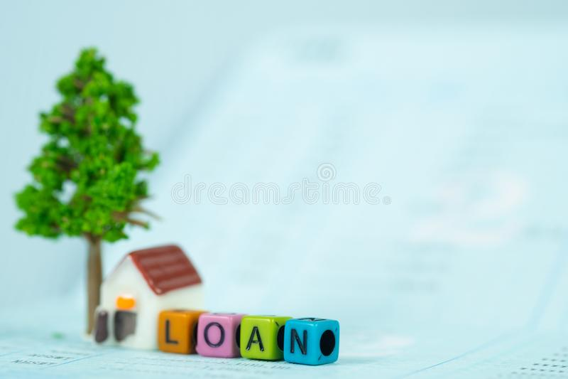 贷款文本和小模式房子和一点树与笔记本, s 免版税库存图片