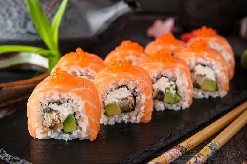 费城与三文鱼,熏制的鳗鱼,黄瓜,鲕梨,乳脂干酪,红色鱼子酱的卷寿司 库存图片