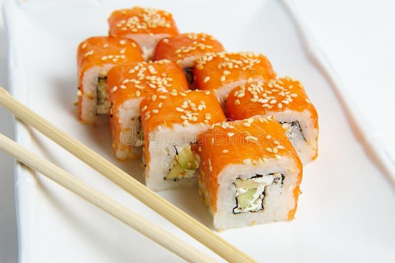 费城在有筷子的一块白色板材滚动 三文鱼 免版税库存图片
