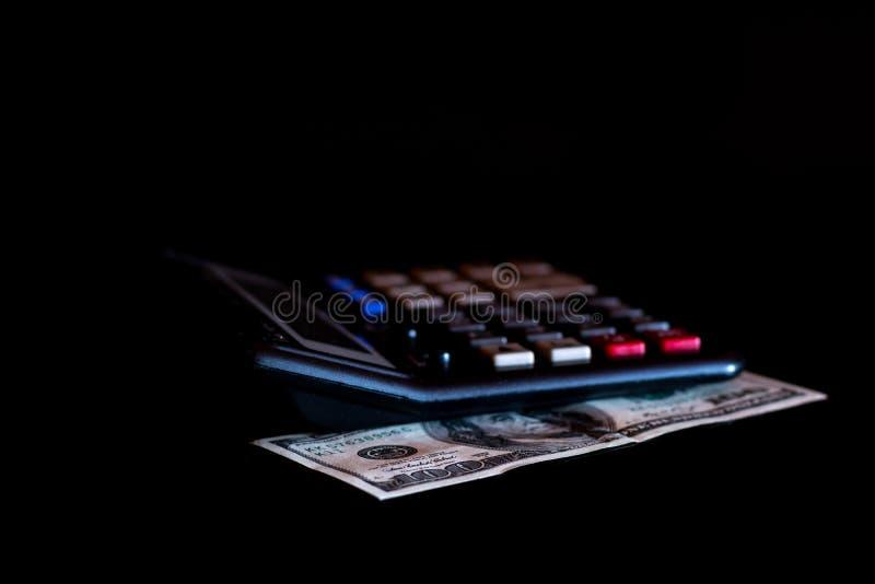 费用花费了,预算和税或者投资演算,与计算器的一百美元在深黑色背景桌上 免版税库存照片