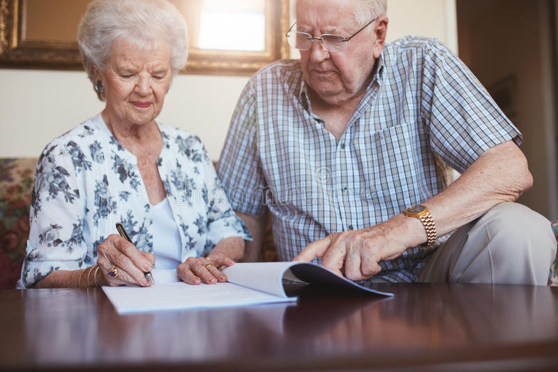 资深一起做文书工作的丈夫和妻子在家 免版税库存照片