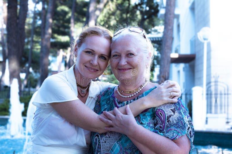 资深一起花费时间的妇女和她的女儿在城市公园 年长妈妈和愉快女儿微笑和拥抱 免版税库存图片