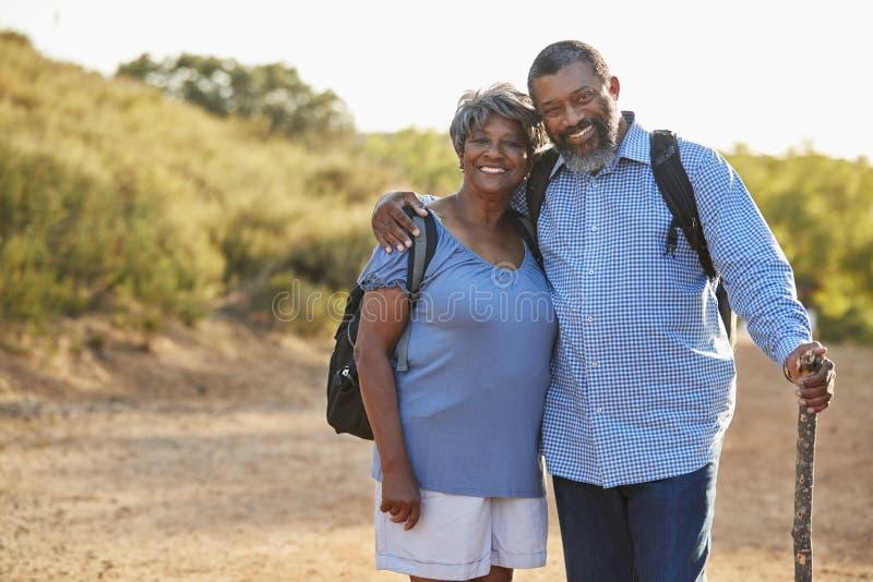 资深一起远足在乡下的夫妇佩带的背包画象  免版税库存照片