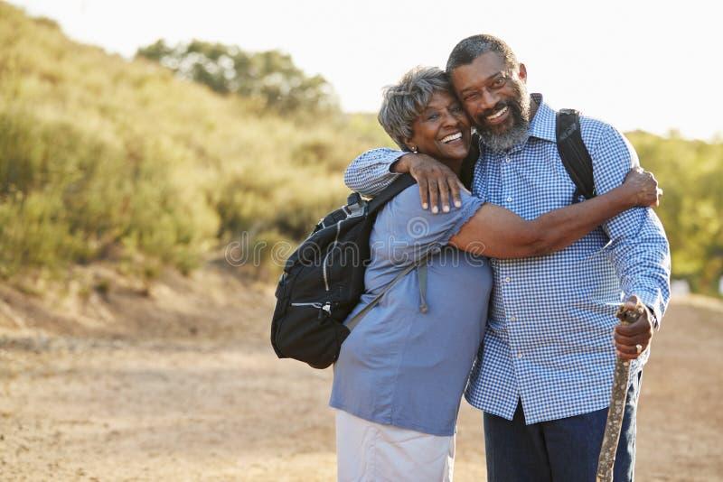 资深一起远足在乡下的夫妇佩带的背包画象  库存图片