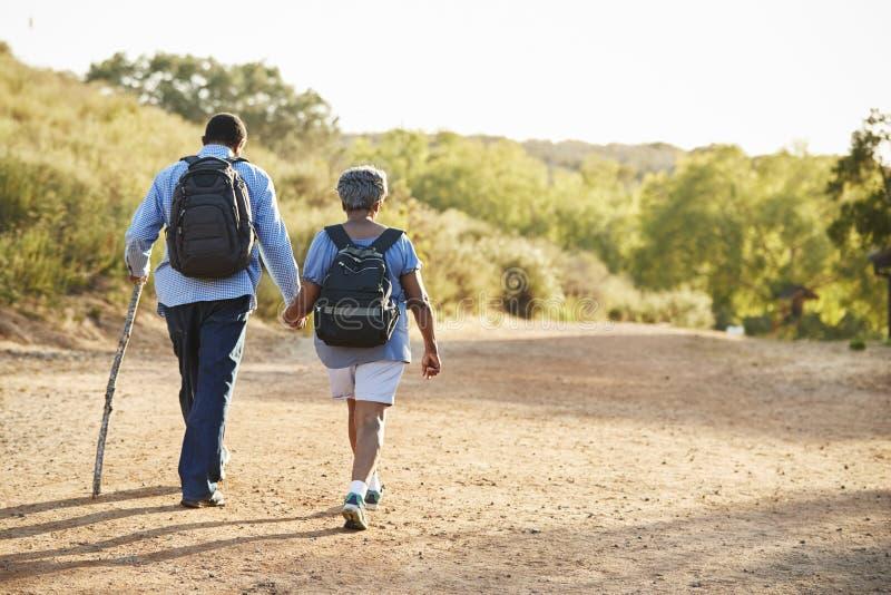 资深一起远足在乡下的夫妇佩带的背包背面图  免版税库存照片